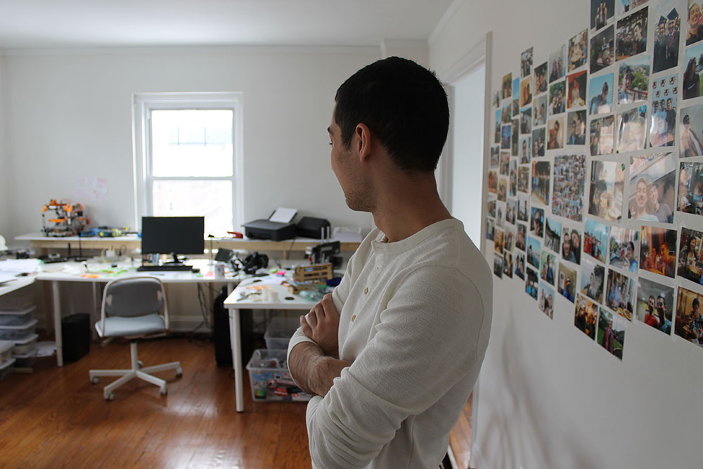 Cyrus Tabrizi pictured in his room, standing between a wall of photos of the people he loves and a set of desks with all the hardware and equipment he uses to work on his ideas. He's looking away from the camera.